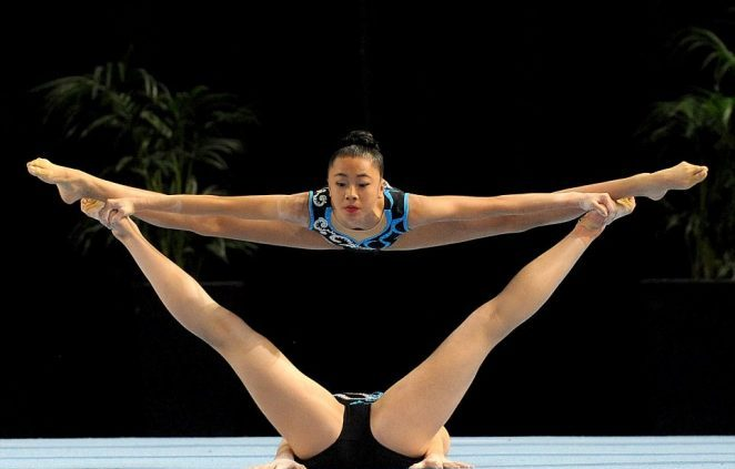 Two woman gymnasts doing flexible patterns on the floor
