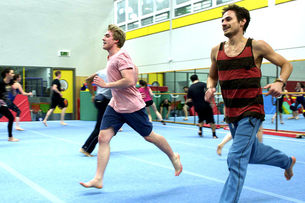 Group of male gymnasts running in a trianing session