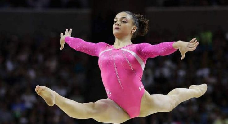 A beautiful young girl gymnast in a pink gymnastic swimsuit